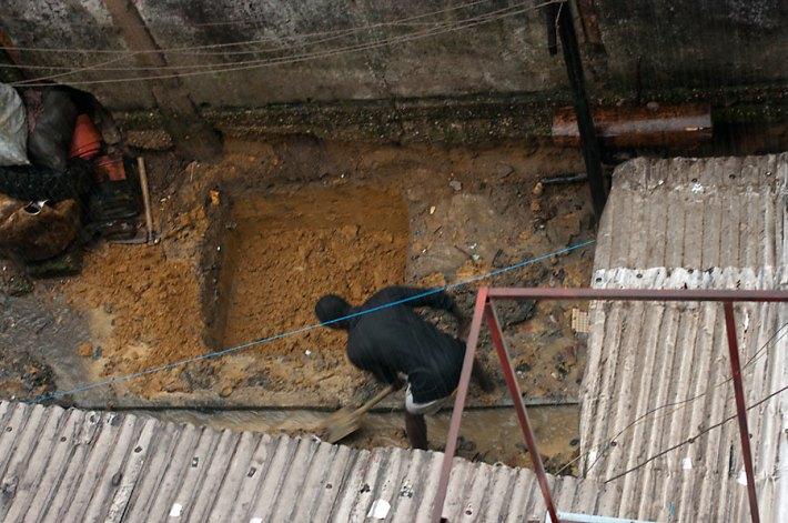 Homme creusant sous la pluie